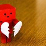 little red cardboard man holding a broken heart